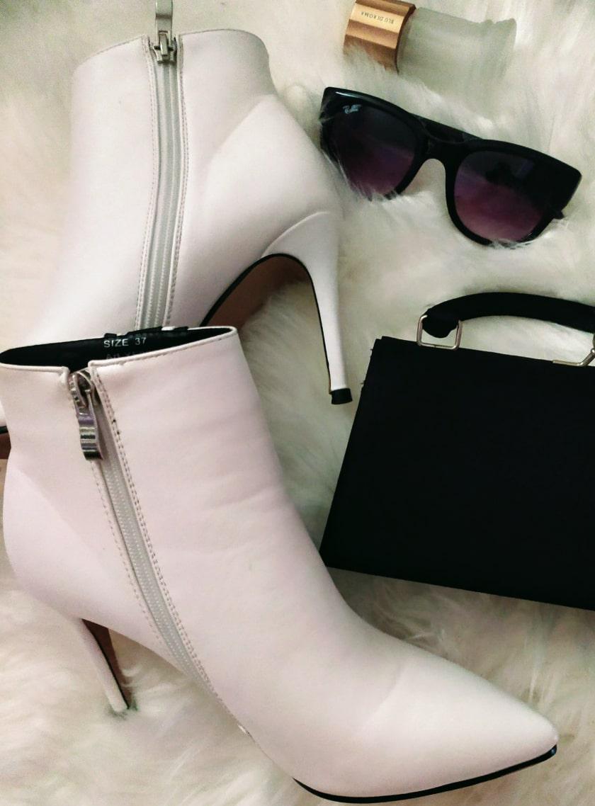 Stivaletti bianchi con tacco a spillo abbinati ad occhiali neri e borsetta nera
